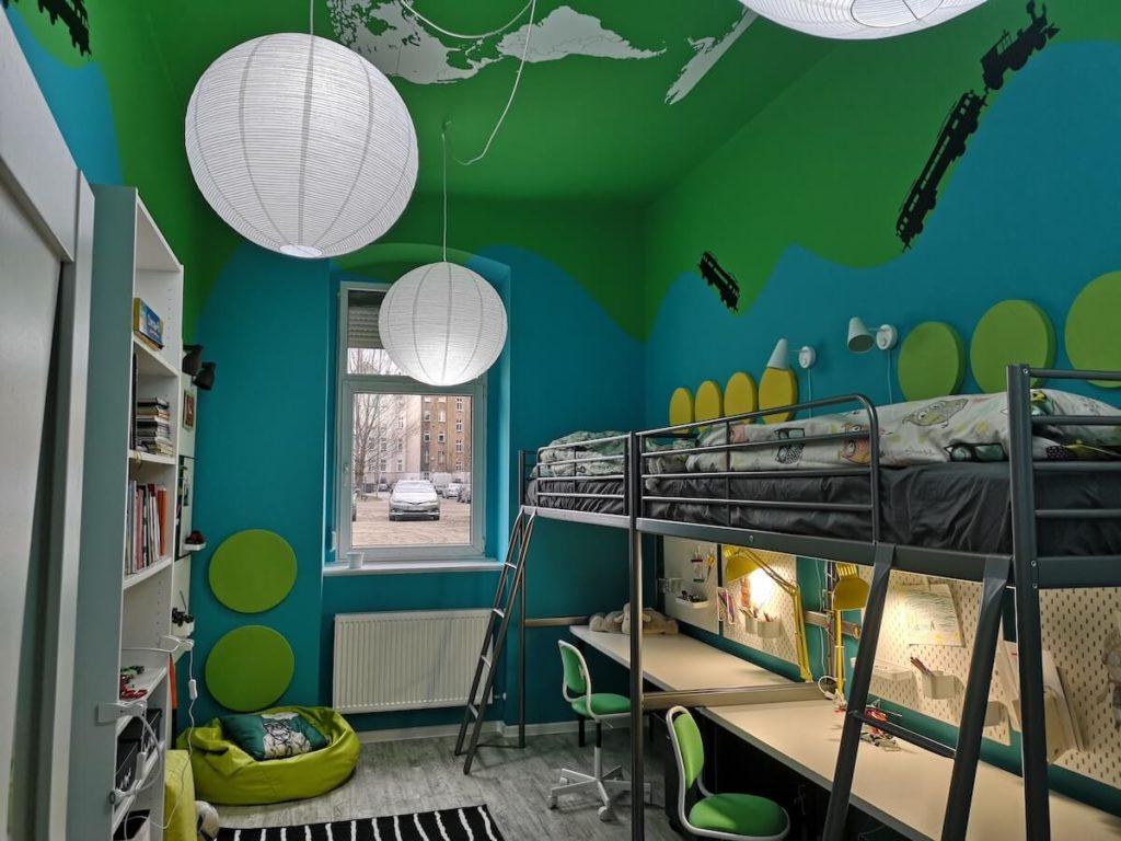 pomalowany pokoj dzieci z naklejkami w pociagi i pietrowymi łożkami