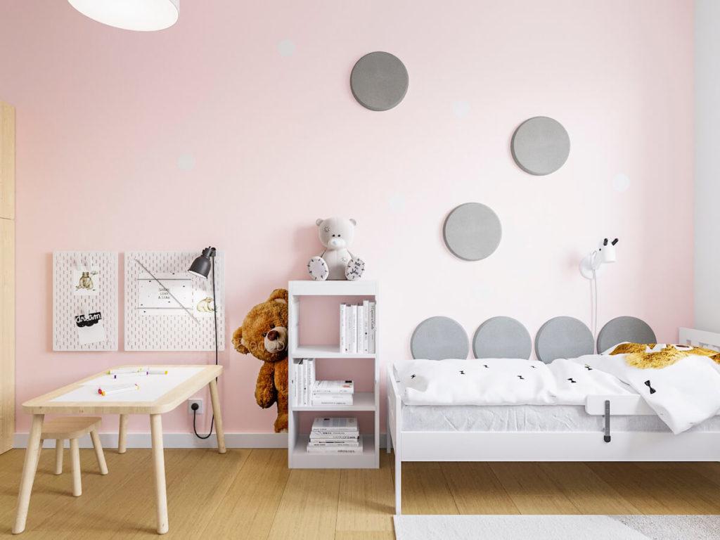 Bladoróżowa ściana w pokoju dziewczynki z łóżkiem i przyklejonymi miękkimi panelami ściennymi
