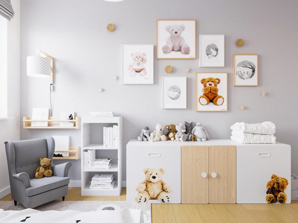 Pokój dziewczynki ze ścianą pomalowaną na szaro, obrazkami z misiami i małym fotelem uszakiem