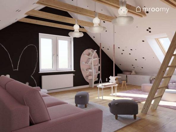 Poddaszowy pokój zabaw dla dwóch dziewczynek z czarną ścianą kredową regałem drzewko i Różową sofą obok której stoją szare pufy świnki