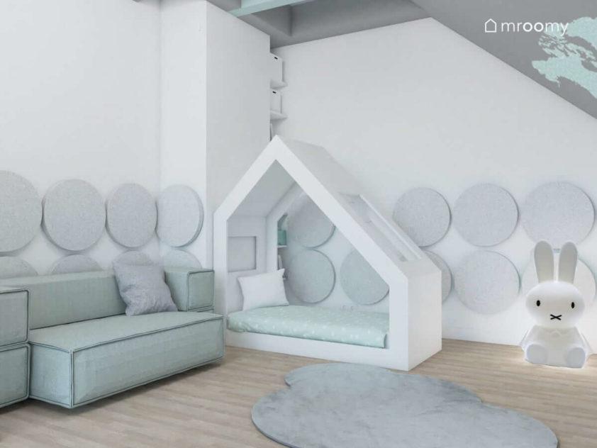 Rozkładana miętowa sofa i łóżko domek na tle ścian w miękkie panele ścienne w pokoju małego chłopca