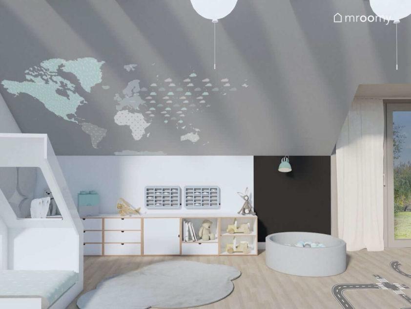 Meble z białej sklejki na tle szarej ściany z naklejką mapą świata w pokoju chłopięcym