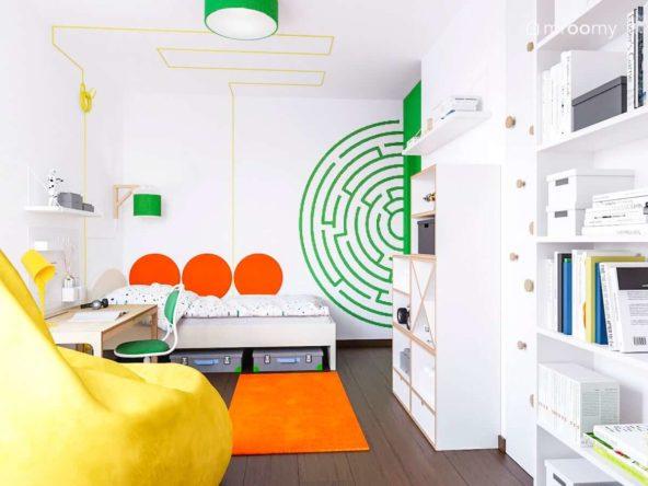 Jasny pokój chłopca z labiryntem na ścianie żółtą pufą i białymi meblami