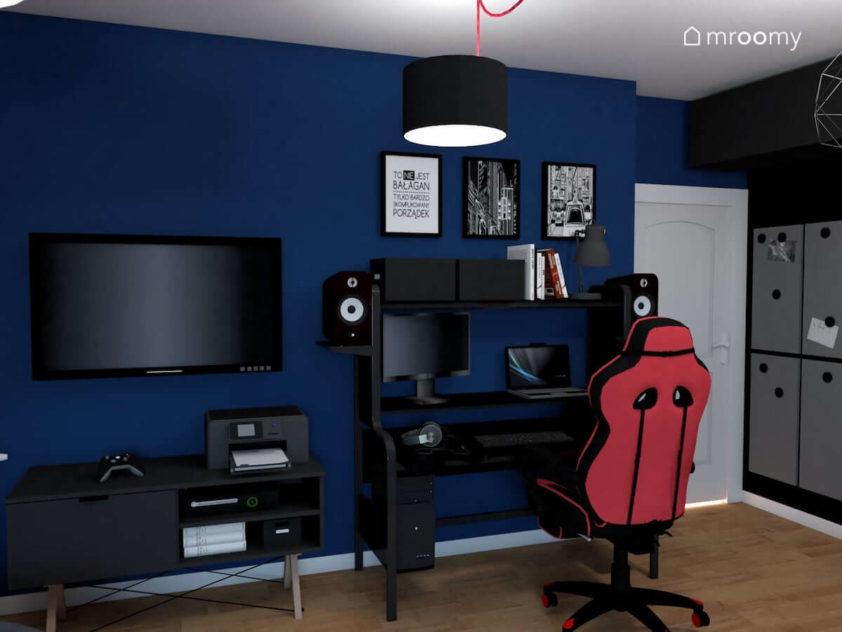 Biurko do grania w gry w pokoju nastolatka w ciemnych kolorach z fotelem i niebieską ścianą