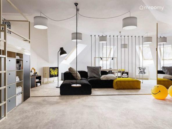 Łózko piętrowe i sofy w dużym pokoju na poddaszu chłopca nastolatka z dużą ilością lamp
