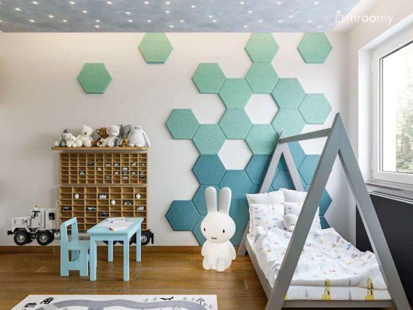 Ściana z panelami ściennymi w kształcie heksagonów i łóżko domek z lampką królikiem w pokoju małego chłopca