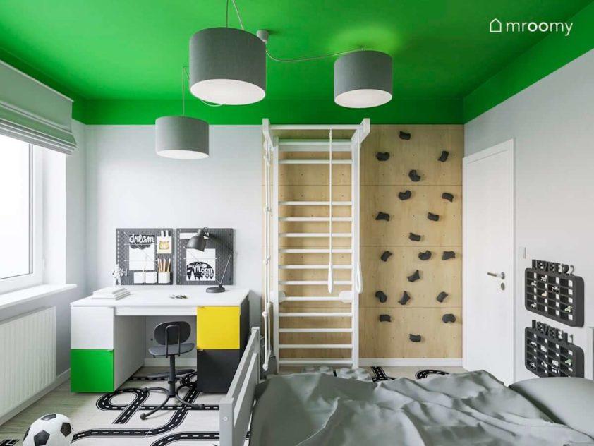 Ścianka wspinaczkowa z drabinką biurko i wygodne krzesło w pokoju 7-letniego chłopca z zielonym sufitem