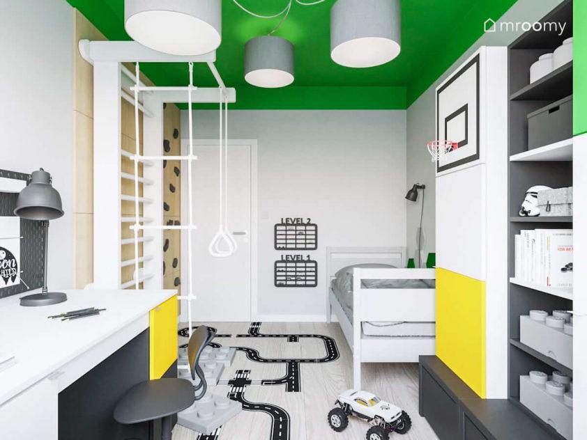 Pokój chłopca z biało-czarno-żółtymi meblami ścianką wspinaczkową i naklejką na podłodze