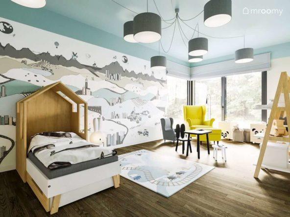 Kolorowa tapeta z motywem krajobrazu i dziecięcy stolik i krzesełko w dużym pokoju małego dziecka