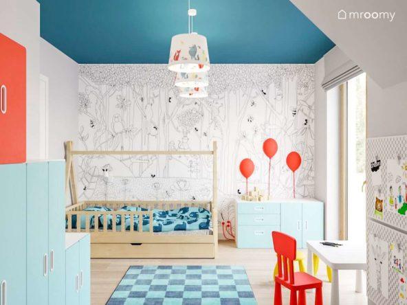 pokój małego chłopca z tapeta z małpkami i dżunglą dywanem w niebieską kratkę łóżkiem tipi i biało niebieskimi meblami
