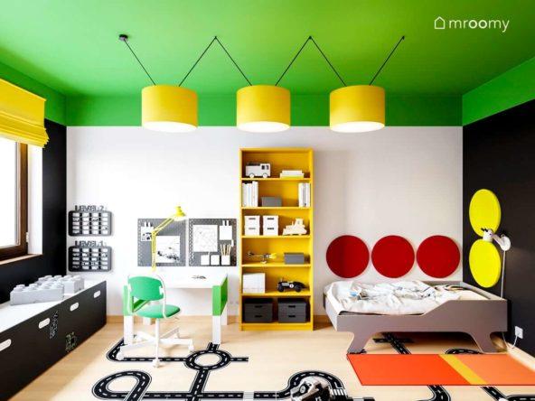 kolorowy pokój małego chłopca z intensywnie zielonym sufitem żółtymi lampami żółtym regałem i czerwonymi okrągłymi panelami na ścianie przy łóżku