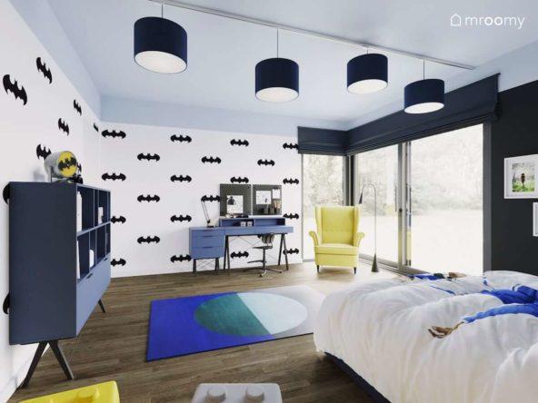 Biała tapeta z czarnymi symbolami Batmana niebieskie meble i dodatki i żółty fotel w pokoju chłopca