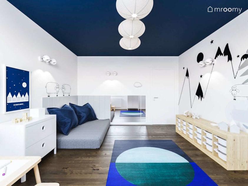 Materac na podłodze jasne meble i ściany w góry i owce w pokoju małego chłopca przedszkolnego z niebieskim sufitem
