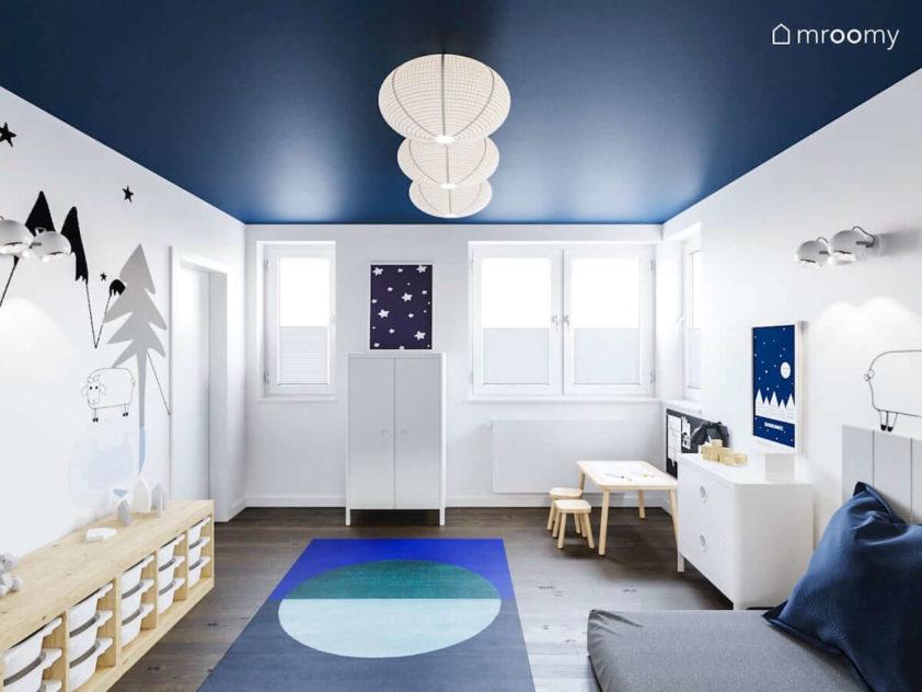 Stolik do rysowania regał na zabawki niebieski dywan biała szafa i miejsce do spania w minimalistycznym pokoju dla małego chłopca