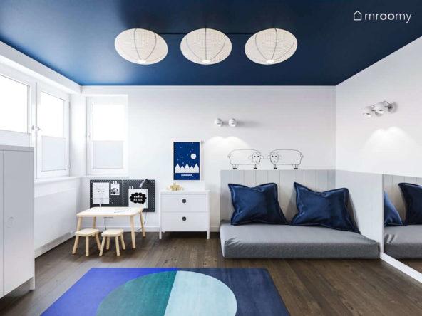 Miejsce do spania z miękkimi panelami ściennymi stoliczek z krzesełkami tapeta w owcami i niebieski dywan w minimalistycznym pokoju małego chłopca
