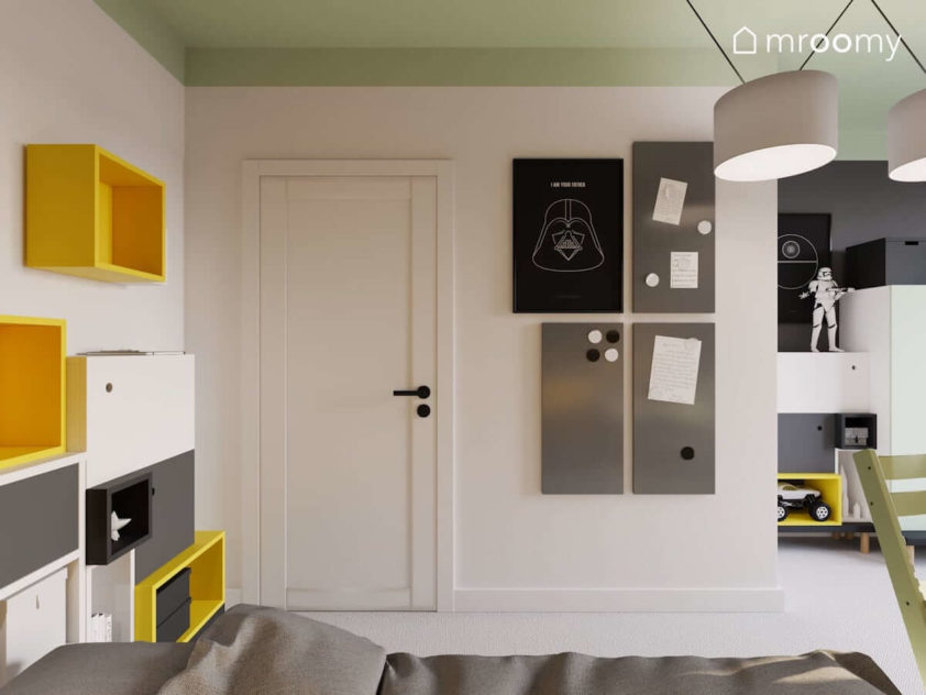 Szare tablice magnetyczne i kolorowy regał obok łóżka w pokoju szkolnego chłopca w którym jest również miętowy sufit