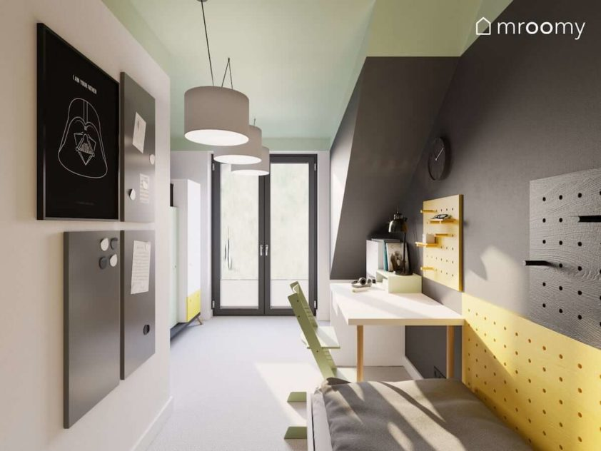 Szara ściana z miejscem do nauki magnetyczne tablice i łóżko w niewielkim pokoju ze skosami  dla chłopca