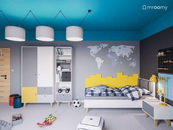 Pokój dziecka z niebieskim sufitem szarymi ścianami i naklejką mapą świata nad białym łóżkiem obok regału młodzieżowego