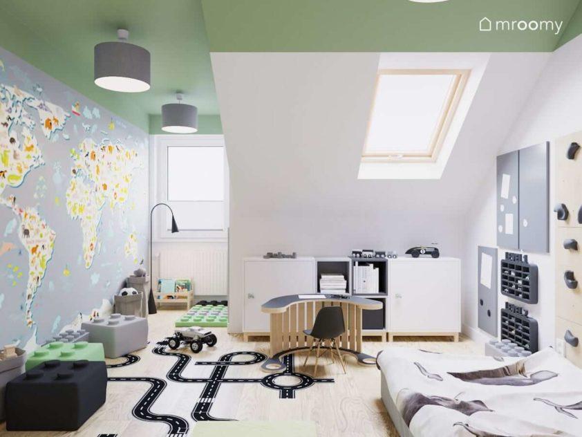 Wielka mapa świata w formie tapety naklejki podłogowe stoliczek z krzesełkiem i materac do spania w pokoju na poddaszu dla chłopca