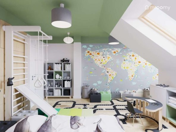 Biała drabinka gimnastyczna ze zjeżdżalnią i duża ściana z mapą świata w pokoju przedszkolaka w kolorach biało-zielonych