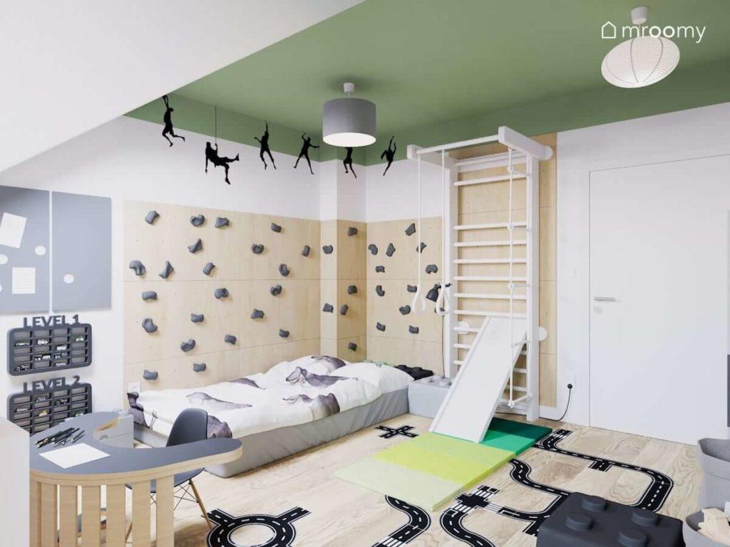 Ścianka wspinaczkowa przy łóżku w pokoju małego chłopca w którym jest również biała drabinka gimnastyczna i zielony sufit