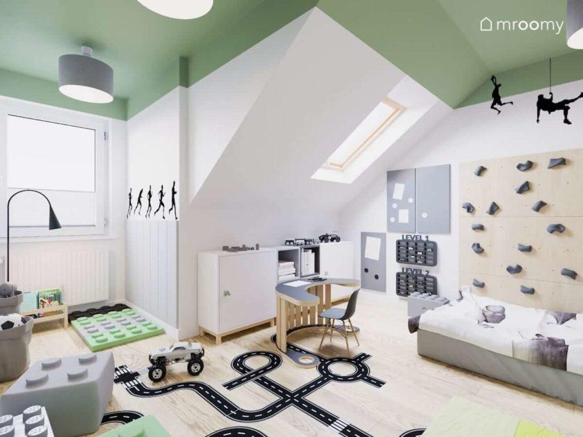 Na ścianie garaże dla aut tablice magnetyczne i organizery ścienne stoliczek i krzesełko w pokoju małego chłopca ze ścianą wspinaczkową i naklejką ulicą na podłodze.