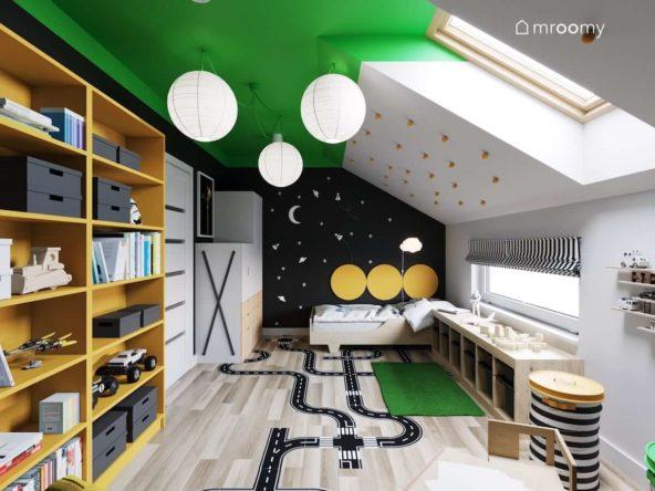 Żółty regał naklejka podłogowa i łóżko na tle czarnej ściany z gwiazdami w pokoju dla chłopca w którym jest zielony sufit