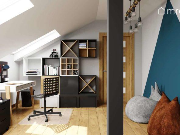 Białe biurko ażurowe czarne i białe regały i ściana z pomalowanym niebieskim trójkątem w pokoju nastolatka