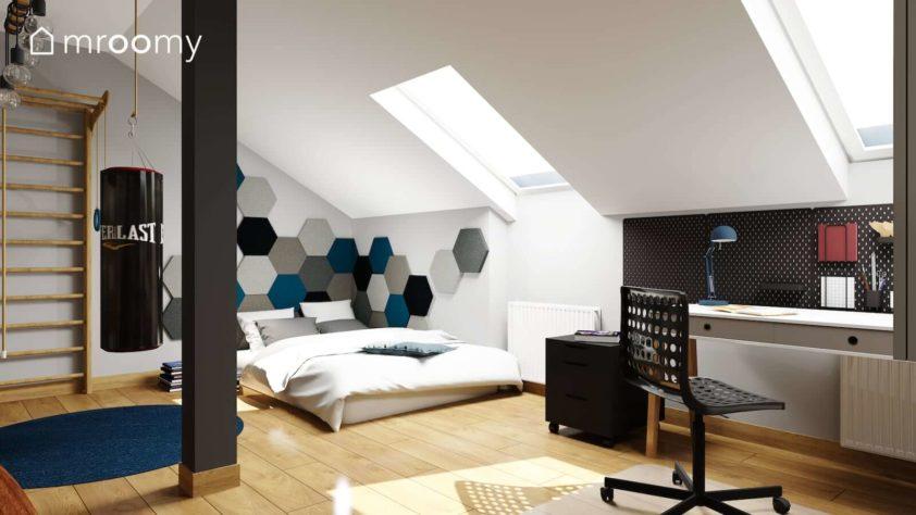 Duży materac do spania z zagłówkiem z miękkich paneli ściennych worek bokserski i drabinka w pokoju nastolatka na poddaszu