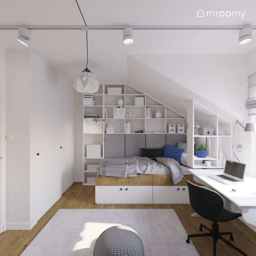 Pokój chłopca ze skosami w którym jest duży regał łóżko biurko i dywan w kolorze białym