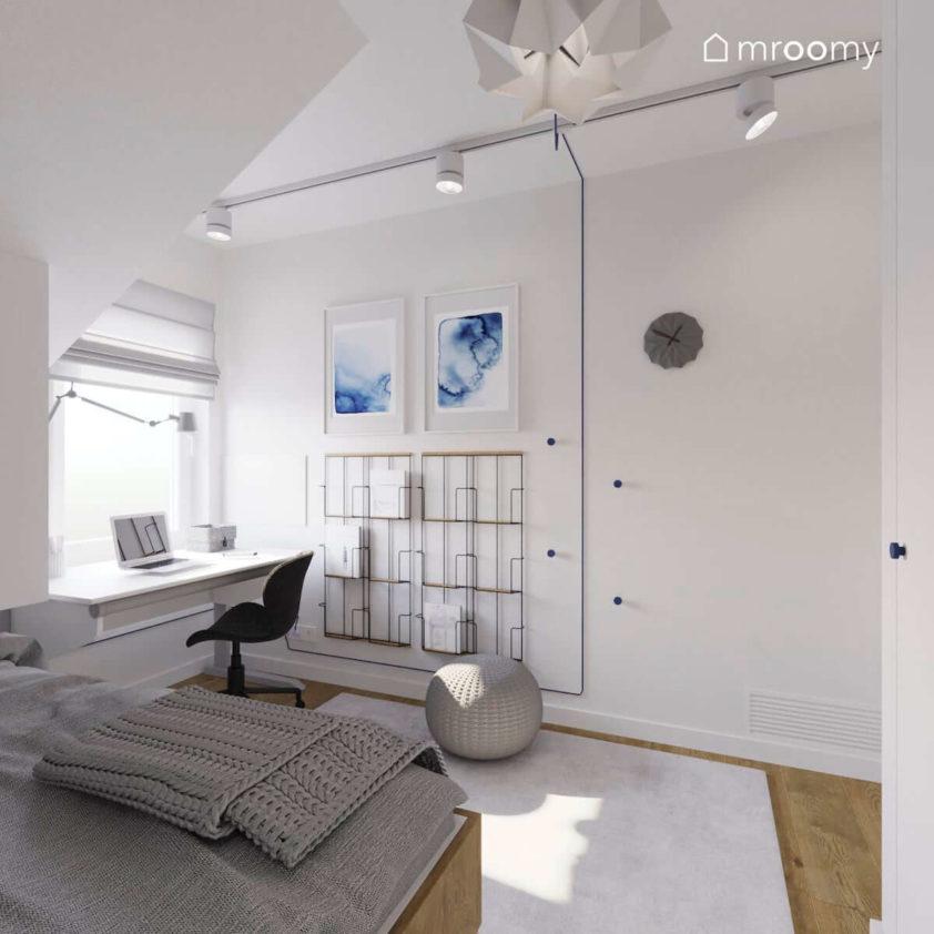 Łóżko i biurko w niewielkim pokoju chłopca na poddaszu gdzie dominuje biel z niebieskimi akcentami i halogenowe reflektory na suficie