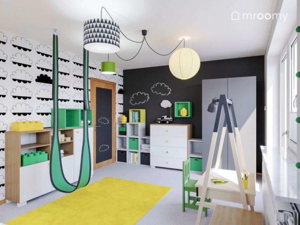 Czarno-biała tapeta w chmury białe i szare meble i zielona huśtawka w pokoju małego chłopca