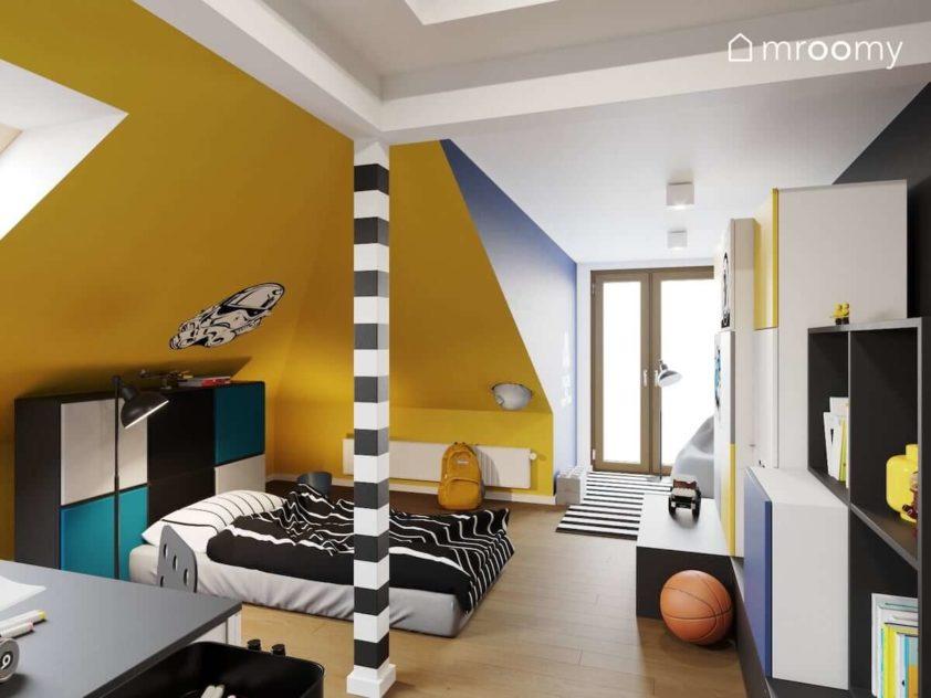 Skosy pomalowane na żółto obok łóżka w formie materaca i zagłówka z mebli z naklejonymi miękkimi panelami ściennymi w pokoju nastoletniego chłopca.