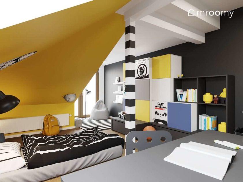 Łóżko w formie materaca leżące na podłodze kolorowe meble na poddaszu z dużymi skosami pomalowanymi na żółto w pokoju nastolatka