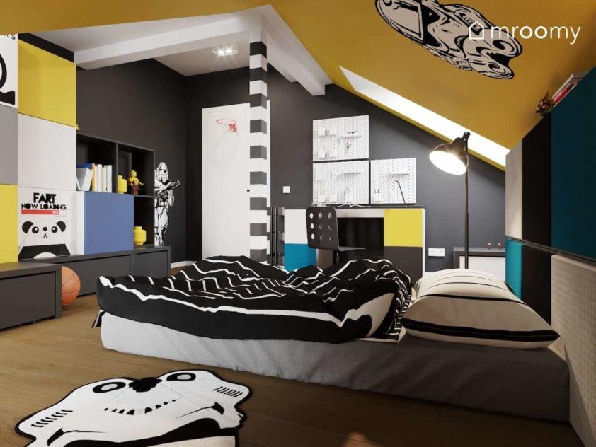 Materac leżący na podłodze kolorowe modułowe meble i czarna ściana w pokoju ze skosami