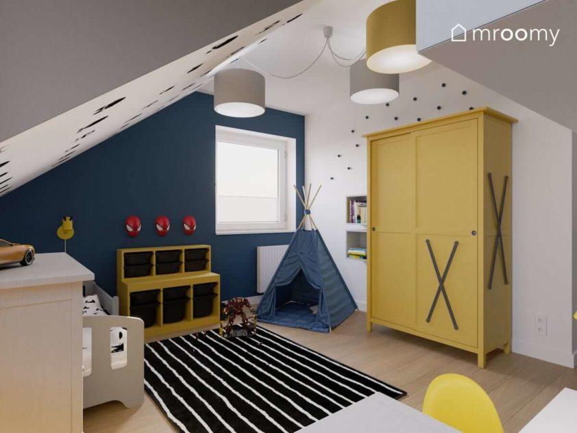 Żółte meble niebieska ściana czarny dywan w paski i namiot tipi w pokoju małego chłopaka
