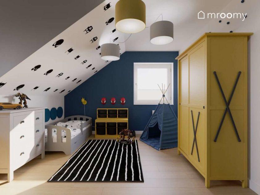 Żółta szafa niebieska ściana i lamy spiderman w pokoju chłopca ze skosami i szarym łóżkiem obok czarnego dywanu