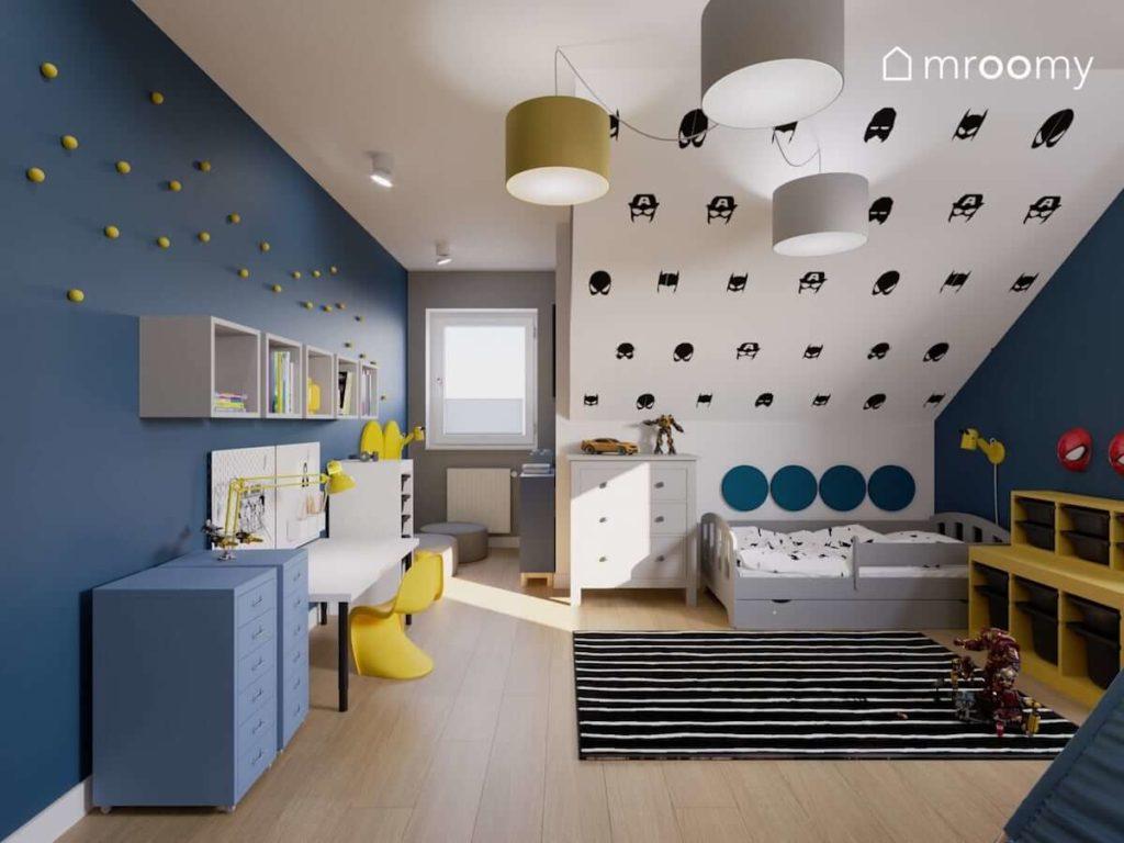 Naklejki z maskami superbohaterów na ścianie ze skosem niebieska ściana szare łóżko i kącik do czytania z miękkimi panelami ściennymi w pokoju małego chłopca