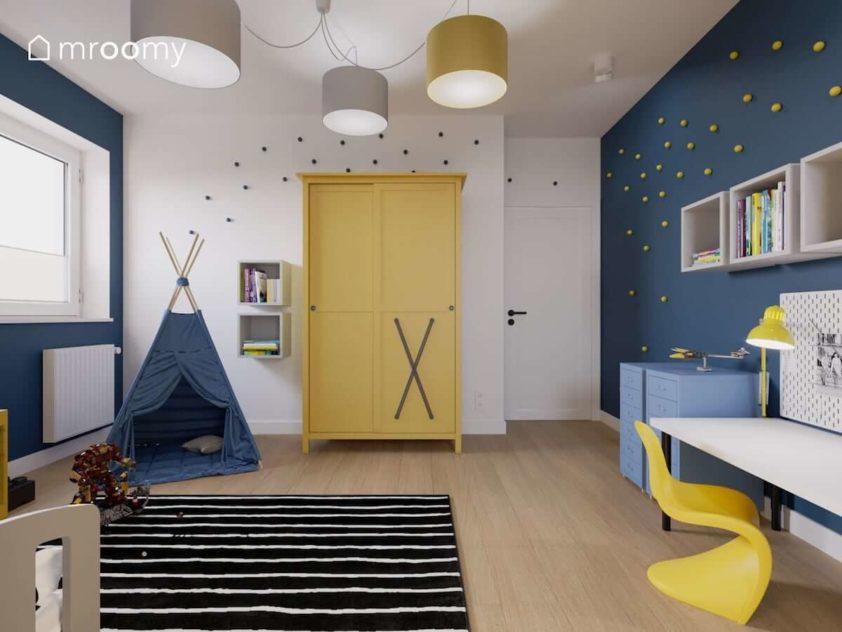 Niebieskie tipi żółta szafa z dodanymi gumowymi strapami i biała ściana z gałkami kropkami w pokoju małego chłopca fana superbohaterów