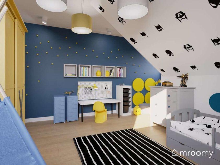 Kącik do nauki chłopca z niebieską ścianą z żółtymi kropkami naklejkami z superbohaterami na ukośnej ścianie i czarnym dywanem w białe paski