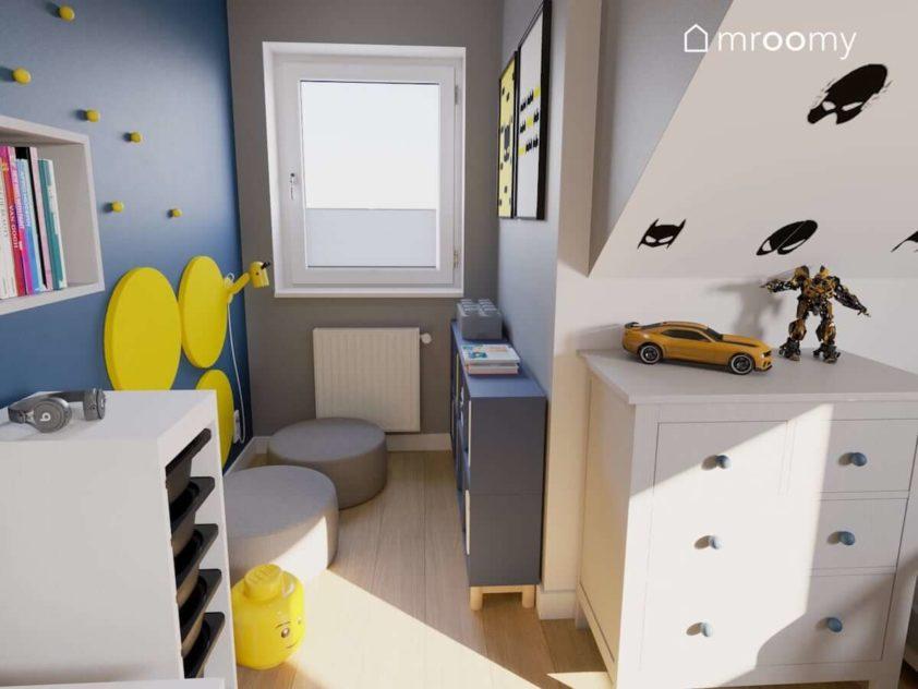 Kącik do czytania dla małego chłopca z miękkimi pufami żółtymi panelami na ścianie i niebieskimi regałami na książeczki