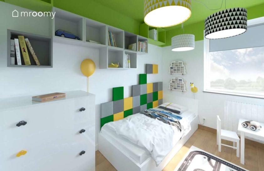 Kwadratowe zielone i szare panele ścienne przy łóżku w pokoju z zielonym sufitem małego fana samochodów.