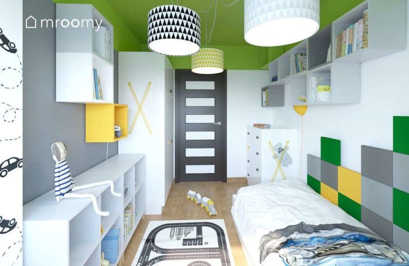 Łóżko regał biała szafa i dywan droga w pokoju małego dziecka z zielonymi i żółtymi elementami.