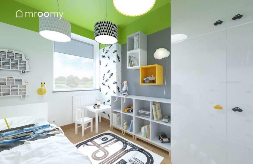 Pokój dla małego chłopca z zielonym sufitem białymi i szarymi ścianami krzesełkiem i stoliczkiem do rysowania i łóżkiem nad którym wiszą półki na samochodziki