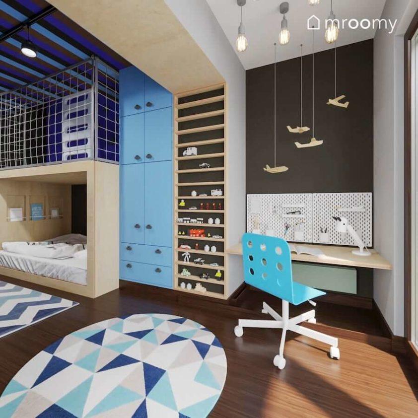 Pojemna szafa w zabudowie z uchwytami w kształcie samochodów i biurko do zabawy w pokoju małego chłopca.