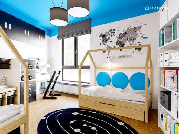 Pokój braci z dwoma łóżkami domkami i biurkiem z krzesłem na podłodze leży czarny dywan z motywem kosmosu a na ścianie naklejka z mapą świata