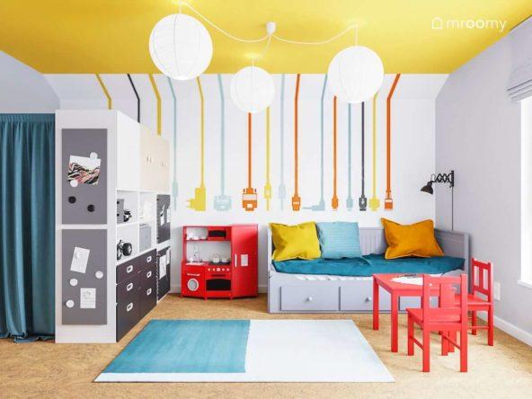Pokój bawialnia dwóch chłopców z kolorową tapetą żółtym sufitem rozkładanym łóżkiem i czerwonym stoliczkiem