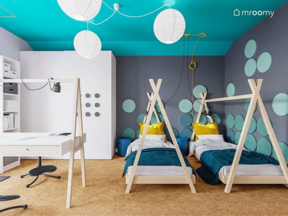 Dwa łóżka tipi na tle szarej ściany z miękkimi panelami ściennymi turkusowym sufitem i białą szafą