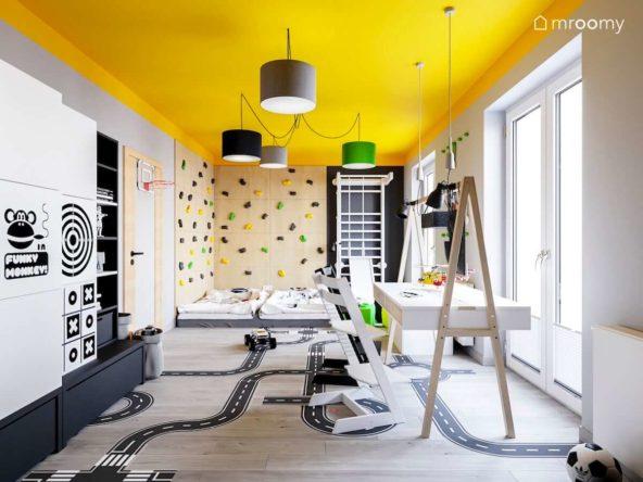 Ścianka wspinaczkowa duży materac podwójne biurko i naklejki z drogą na podłodze w pokoju rodzeństwa