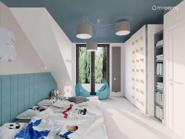 Sypialnia trzech chłopców z materacami i ścianą wyłożoną miękkimi turkusowymi panelami ściennymi kolorowym sufitem szarymi lampami i szafą przesuwną